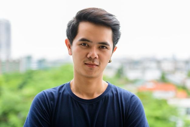 屋外の街の景色に対する若いアジア人の肖像画