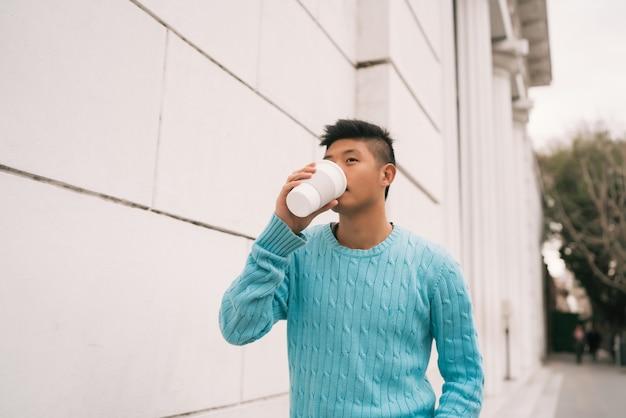 通りで屋外を歩きながらコーヒーを飲む若いアジア人男性の肖像画。アーバンコンセプト。