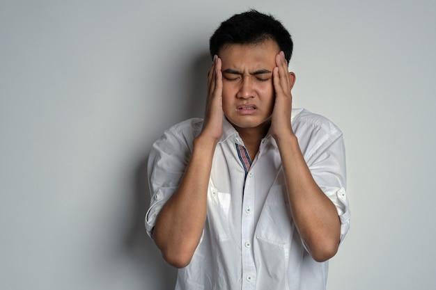 열과 두통을 동시에 앓고 있는 젊은 아시아 남자의 초상화 두통이 있는 남자
