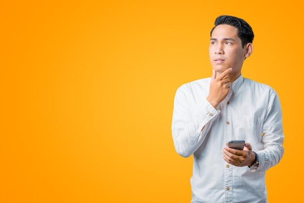 スマートフォンを持ち、あごに手を当てて見上げるアジアの若者のポートレート Premium写真