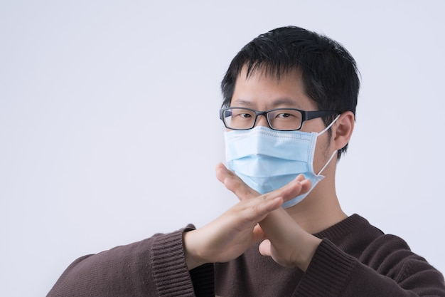 若いアジア人男性の肖像画、白い背景で隔離の医療用サージカルブルーフェイスマスクを着用してコロナウイルス感染にノーと言って、クローズアップ、クローズアップ。