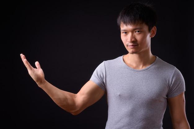 Портрет молодого азиатского человека, показывающего что-то