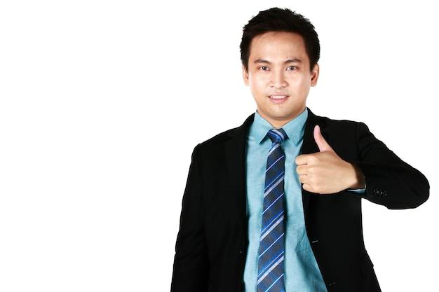 검은 양복을 입고 흰색 배경에 격리된 엄지손가락을 가리키며 웃고 있는 젊은 아시아 남자의 초상화.