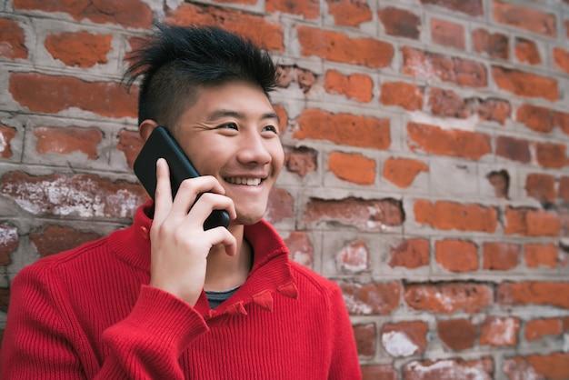 レンガの壁に対して屋外で電話で話している若いアジア人の肖像画。コミュニケーションの概念。