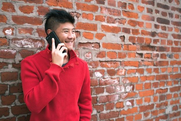 レンガの壁に向かって屋外で電話で話している若いアジア人男性の肖像画。コミュニケーションの概念。