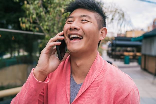 通りの屋外で電話で話している若いアジア人男性の肖像画