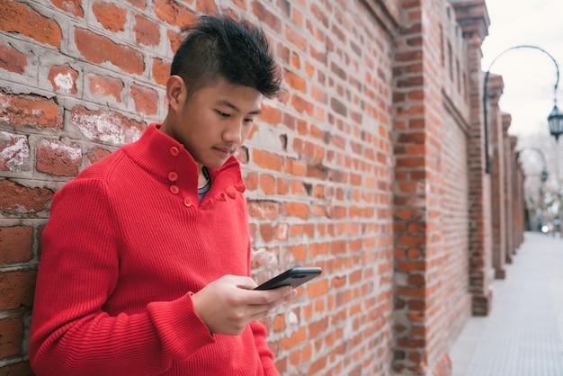 レンガの壁に彼の携帯電話を屋外で使う若いアジア人の肖像画。コミュニケーションの概念。