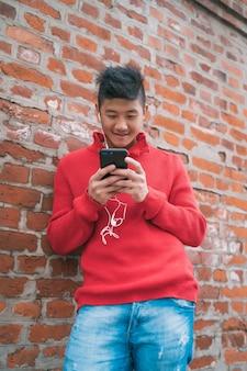 レンガの壁に屋外でイヤホンと彼の携帯電話を使用して若いアジア人の肖像画。コミュニケーションの概念。
