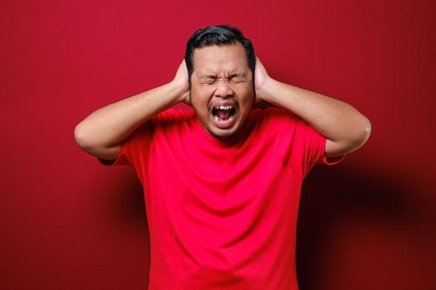 Портрет молодого азиатского мужчины в повседневной красной рубашке, закрывающего глаза и уши, не хочет и не избегает слышать плохие новости, стресс под психологическим давлением на красном фоне