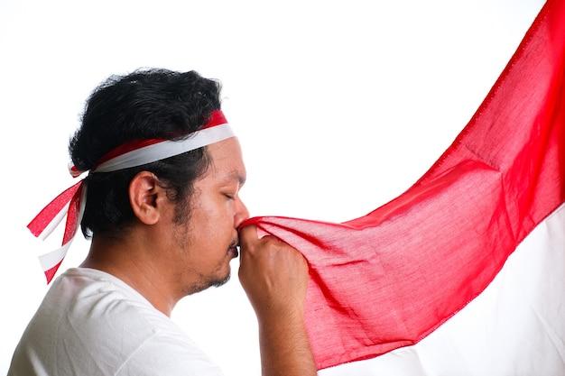 격리 된 흰색 배경 위에 인도네시아의 빨간색과 흰색 국기에 키스 하는 머리띠를 착용 하는 젊은 아시아 남자의 초상화