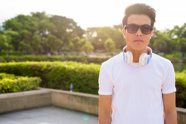 Портрет наушников и солнечных очков молодого азиатского человека нося пока ослабляющ на парке в бангкоке, таиланде