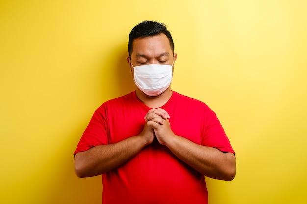 コロナウイルスに対する保護マスクを着用し、コロナウイルスの祈りをしている若いアジア人男性の肖像画は、黄色の背景に分離されてすぐに克服されます