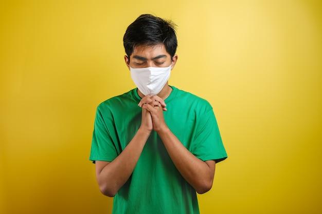 コロナウイルスに対する保護マスクを身に着けて、コロナウイルスのために祈る若いアジア人男性の肖像画は、黄色に分離されてすぐに克服されます