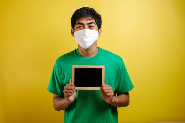 コロナウイルスに対する保護マスクを着用し、黄色の背景に小さな黒板を保持している若いアジア人男性の肖像画