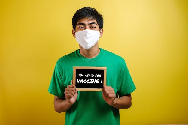 コロナウイルスに対する保護マスクを着用し、黄色の背景に対するワクチンの準備ができていると書かれた小さな黒板を持っている若いアジア人男性の肖像画