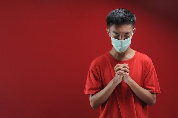 赤のコロナウイルスに対する保護マスクを身に着けている若いアジア人男性の肖像画
