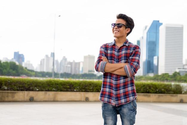 Портрет солнечных очков молодого азиатского человека нося пока ослабляющ на парке в бангкоке, таиланде