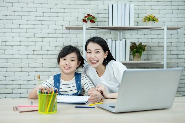 Портрет молодой азиатской матери и дочери используют компьтер-книжку, цветной карандаш и книгу, останавливая ее девочка, делая домашнюю работу.