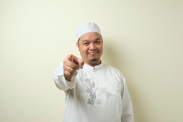 카메라를 보고 앞으로 가리키는 젊은 아시아 이슬람 남자의 초상화. 선택적 초점으로 누군가의 개념 선택