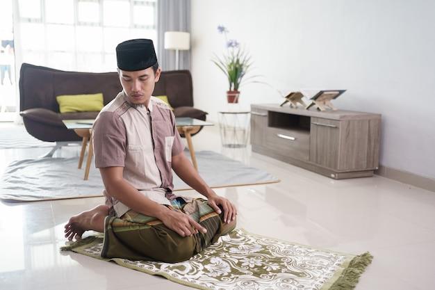Портрет молодого азиатского мусульманина, молящегося дома