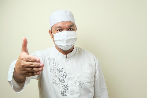 악수를 하고 웃고 있는 마스크를 쓴 젊은 아시아 이슬람 남성의 초상화
