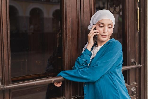 야외에서 휴대전화로 통화하는 젊은 아시아 이슬람 학생 여성의 초상화