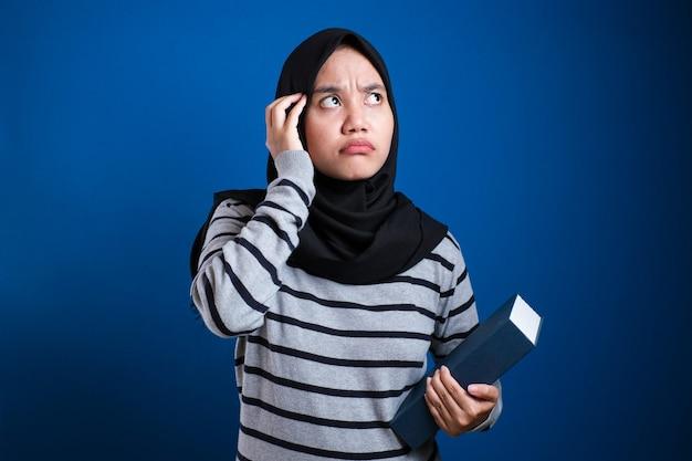 若いアジアのイスラム教徒の女性の肖像画は、青い背景で隔離、指を上に向けて、良いアイデアのジェスチャーを持って笑っている