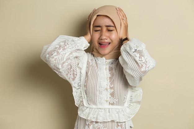 Hijab를 입고 젊은 아시아 이슬람 여자의 초상화는 그녀의 귀를 커버