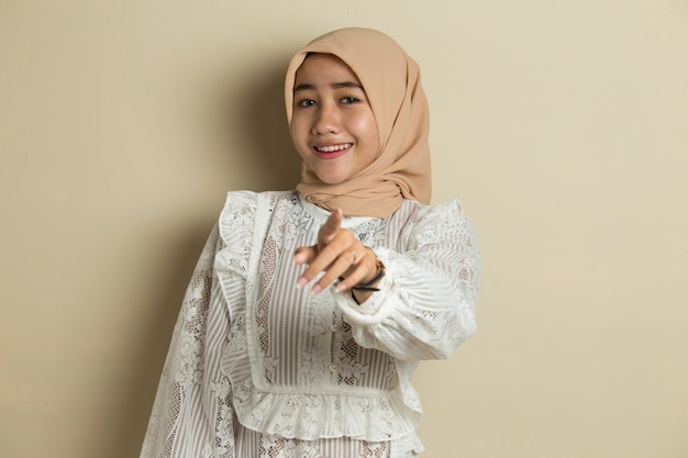 앞으로 가리키는 동안 웃 고 hijab를 입고 젊은 아시아 이슬람 여자의 초상화