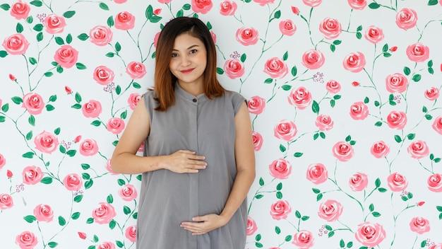Портрет молодой азиатской беременной женщины, улыбаясь стоя, касаясь ее живота, глядя в камеру на фоне образца белых роз. концепция здоровой и счастливой дамы.