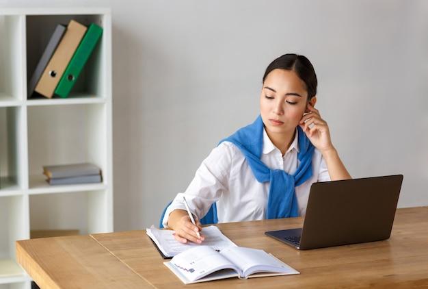 Портрет молодой азиатской женщины-секретаря, сидящей за столом и использующей портативный компьютер во время работы в офисе