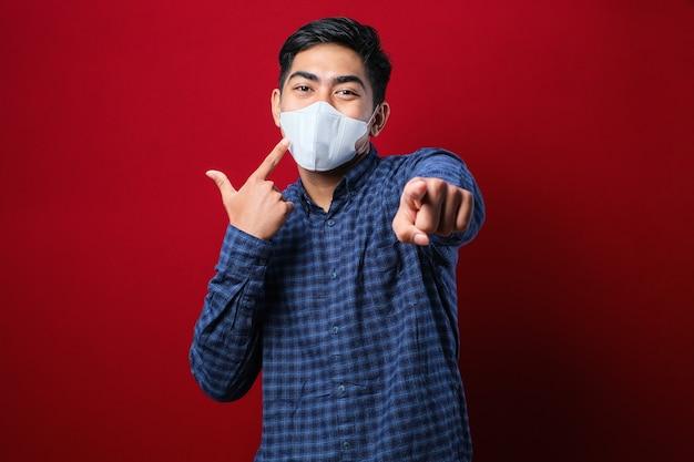 플란넬 셔츠와 앞을 가리키는 마스크를 쓴 젊은 아시아 학생의 초상화, 빨간색 배경에 대해 마스크를 착용할 사람을 선택하는 카메라를 바라보고 있습니다. 프리미엄 사진