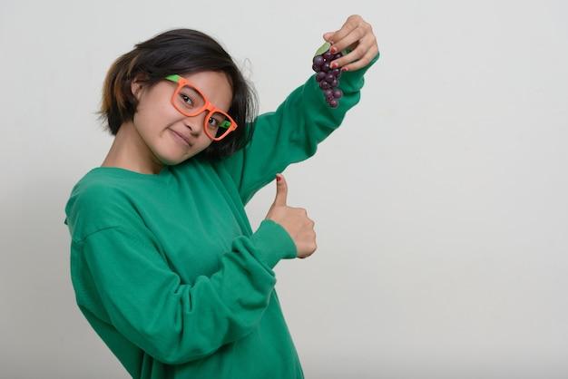 Портрет молодой азиатской девочки-подростка с короткими волосами на белой стене