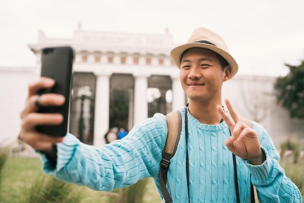 通りの屋外で携帯電話で自分撮りをしている若いアジア人観光客の肖像画。旅行とテクノロジーのコンセプト。