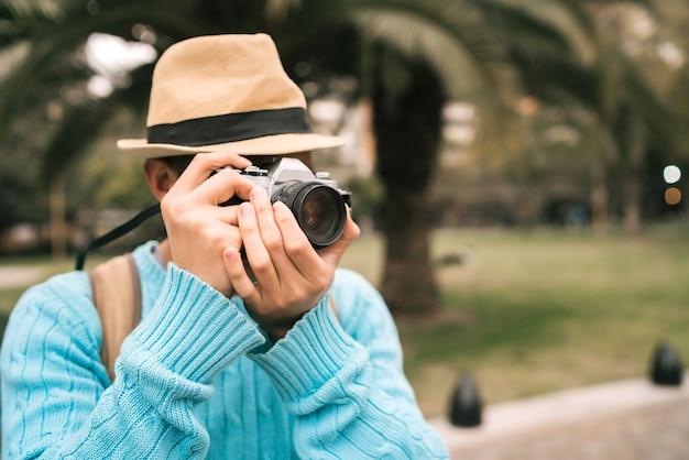 ヴィンテージカメラと屋外の通りでいくつかの写真を撮る若いアジア人観光客の肖像画。旅行のコンセプト。