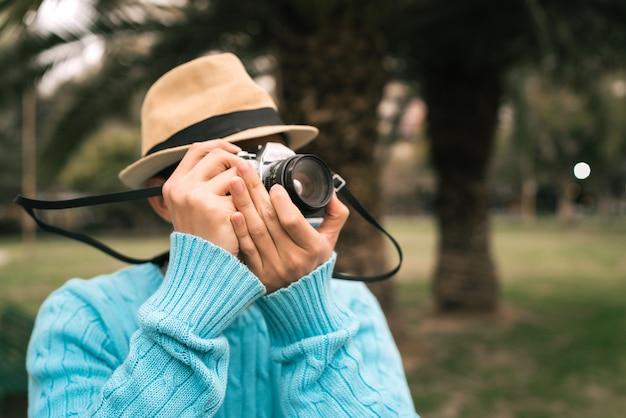 빈티지 카메라와 거리에서 야외에서 몇 가지 사진을 찍고 젊은 아시아 관광객의 초상화.