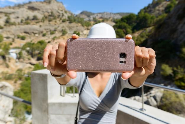 Портрет молодой азиатской туристической женщины, делающей селфи с мобильным телефоном в горах