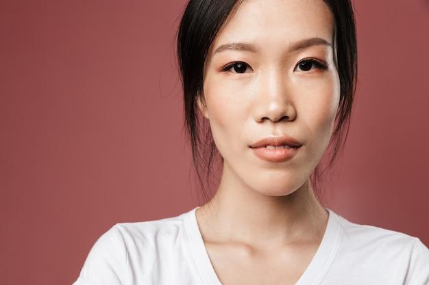 붉은 벽에 격리된 아름다운 시선으로 기본 옷을 입은 젊은 아시아 여성의 초상화