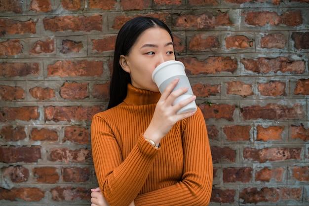 Портрет молодой азиатской женщины, пьющей чашку кофе против кирпичной стены. городская концепция.