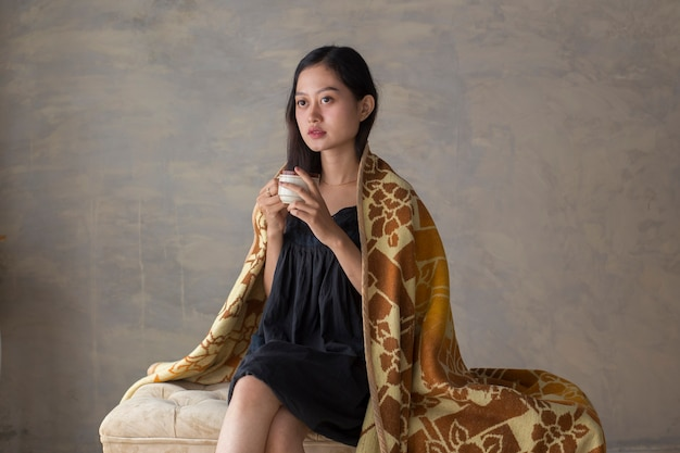 Портрет молодой азиатской женщины, пьющей кофе и расслабляющейся на диване