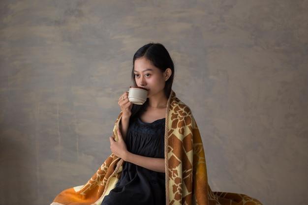 コーヒーを飲み、ソファでリラックスして若いアジアの女性の肖像画
