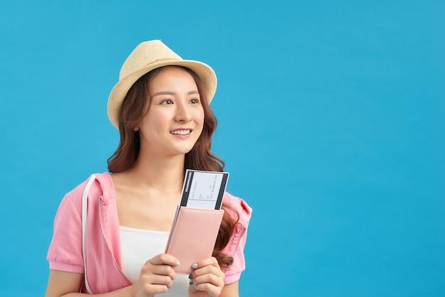 パスポートと笑顔を保持している若いアジアの女性の肖像画。幸せな人々と旅行のコンセプト。