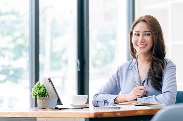 Портрет молодой азиатской женщины держа ручку, усмехаясь и смотря камеру пока сидел на ее офисе стола.