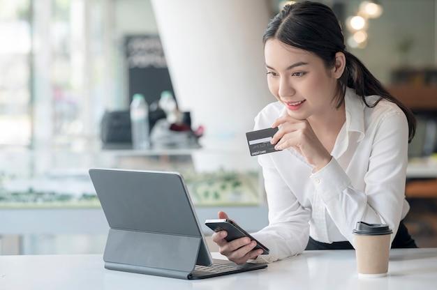 Портрет молодой азиатской женщины держа смартфон и кредитную карту, сидя за офисным столом.