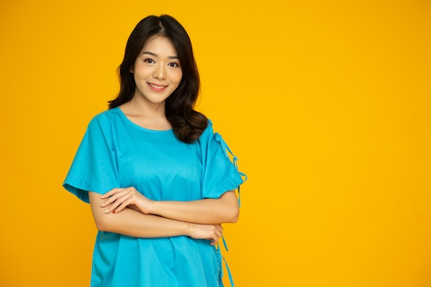 노란색 배경에 격리된 파란색 환자복을 입은 젊은 아시아 여성의 초상화