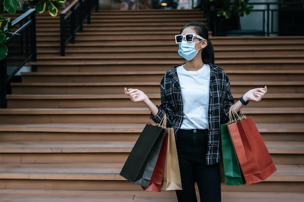 Портрет молодой азиатской женщины в маске в очках, стоящей на лестнице с бумажным пакетом для покупок