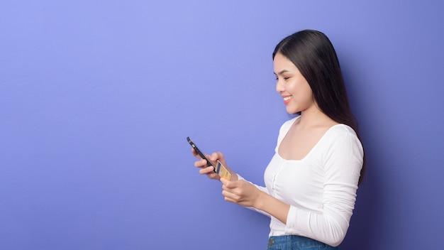 若いアジアの女性の肖像画は紫色の背景にクレジットカードで携帯電話を使用しています。