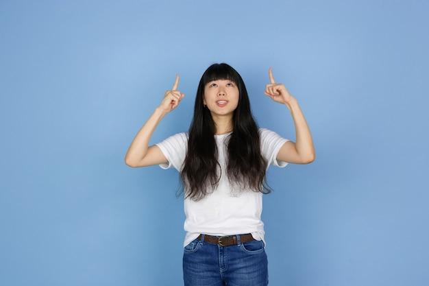 블루 스튜디오 배경에 고립 된 젊은 아시아 여자의 초상화