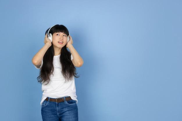 블루에 고립 된 젊은 아시아 여자의 초상화