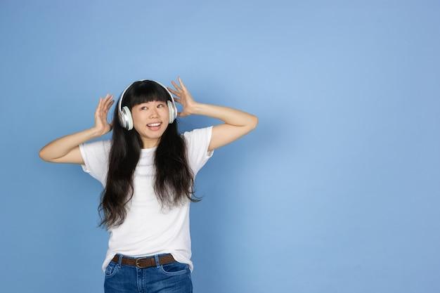 青で隔離の若いアジアの女性の肖像画